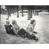 1878 Press Photo Three sledders race down hill, all smiling - spb12899