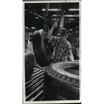 1982 Press Photo Goodyear Employee Lifts Aircraft Tire for Visual Inspection