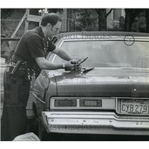 1980 Press Photo Police Officer Wally Cusisk examines Weapon in Washington