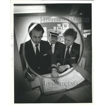 1987 Press Photo Airline Personnel looking at flight schedule - hca03247