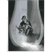 1989 Press Photo Kris Hanson and daughter Tricia ride a slide at Splash-Down