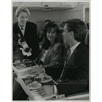 1993 Press Photo Delta airlines flight attendant serving passengers - mja96425