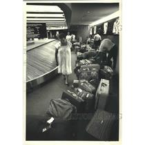1987 Press Photo Travelers at Luggage Carousel in Mitchell International Airport