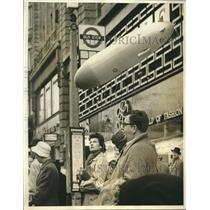 1962 Press Photo A Londoner holds a floating dirigible on his bus ride