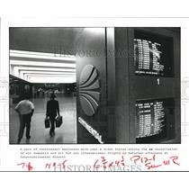 1983 Press Photo Continental Airlines Employees Walk Past Video Display, Houston