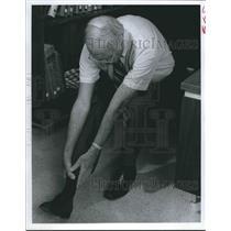 1978 Press Photo Man demonstrates bending exercise at his desk - hca24045