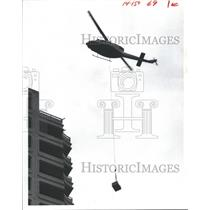 1982 Press Photo Helicopter lifts equipment to top of condo under construction