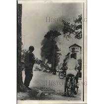 1955 Press Photo Vietnamese solider and civilian watch smoke in Saigon