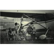 1985 Press Photo Family seeks shelter from rain under wing of plane, Oshkosh