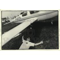 1994 Press Photo Bart Cleary rests in shade of plane wing at Wittman Airport