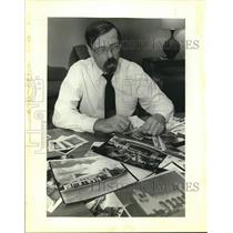 1954 Press Photo Vaughn Bombarder at desk with photos, Texas - saa01884