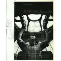 1993 Press Photo Ernest Serafino look up at gunnery tower of WWII airplane