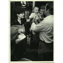 1984 Press Photo Man holds Joshua Akil with mother Brenda at airport in Alabama