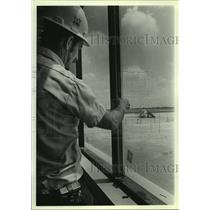 1986 Press Photo Construction worker installs window at new Alabama airport