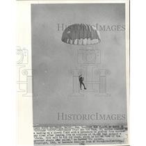 1964 Press Photo Stuntman Rod Pack floats to Earth on borrowed parachute.