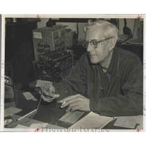 1955 Press Photo DeVon Hough checks his watch while writing poetry. - RSH17961