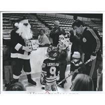 1989 Press Photo Boston Bruins Coach Terry O'Reilly Santa Presents Children
