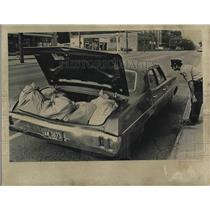 1973 Press Photo Police Officer Investigating Car with Open Trunk and Bags