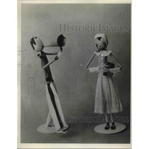 1933 Press Photo Two carved wooden dolls on display