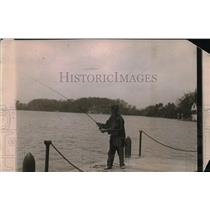 1919 Press Photo man standing lakeside on dock fishign
