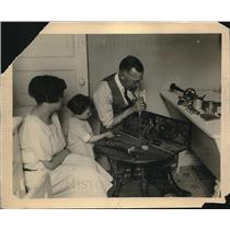 1924 Press Photo Child & Mother Watch While ad Fixes Radio
