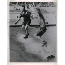 Press Photo Two men in a log rolling contest in a pool
