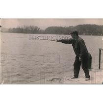 1919 Press Photo A local anglers casting his reel to fish in the docks