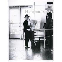1960 Press Photo Passenger reads paper waiting for plane at Haphius airport