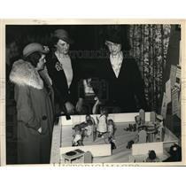 1933 Press Photo Mrs. H Van Y Caldwell, Miss Sophia J Arc looks at play dolls