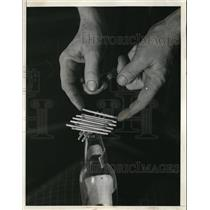 1936 Press Photo Thomas HB Staggers stacking matches on a bottle