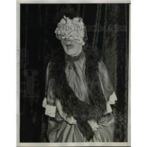 1938 Press Photo Slipping on a mask and a wrap