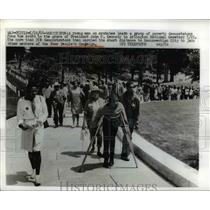 1968 Press Photo of a young man on crutches leading demonstrators from the grave