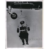 1955 Press Photo of a British Naval Officer in Bosun's chair suspended under a