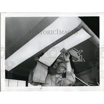 1959 Press Photo A worker puts decals & marking on a plane