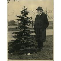 1922 Press Photo Edward K. Bhapman, looking in a Xmas Trees