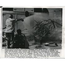 1956 Press Photo Firemen pour water on wreckage of sightseeing plane