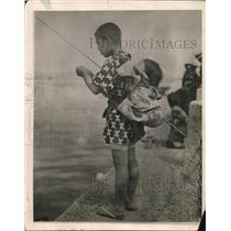 1920 Press Photo Japanes boy & baby on his back fish at a shoreline