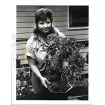 1988 Press Photo Cathee Thomas, bringing potted plants indoor for the winter