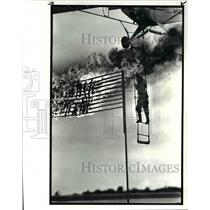 1986 Press Photo Johnny Kazian dangles from ladder below piper super cub