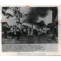 1955 Press Photo Refugees, one of them carrying a wounded child