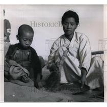 1951 Press Photo Widowed mother from Seoul cleans grains at rice distribution