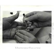 1985 Press Photo A sample of the blood is taken from the finger to check for
