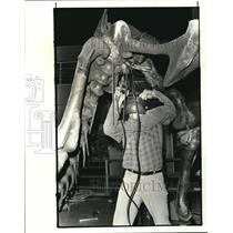 1983 Press Photo Tim Riedel, building supervisor works a the dinosaur's brace