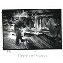 1989 Press Photo Worker cuts sheet rubber at Burton Rubber Co in Burton OH