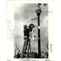 1992 Press Photo Eric Siegmund hangs a May basket in downtown Gresham