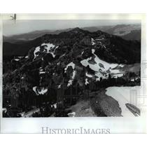 1974 Press Photo Icy snow banks contrast with green meadows in the backcountry