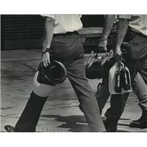 1972 Press Photo Officials carrying helmets, radios and locked bags to a plane