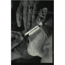 1985 Press Photo Emery deftly stroked the razor over the customer's face