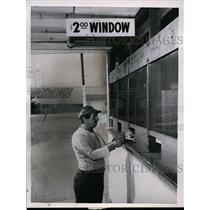 1961 Press Photo Man at a betting window places bet at Cinncinati Ohio