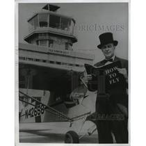 "1965 Press Photo Stunt Pilot Captain Dick Schramm Reading ""How to Fly"""